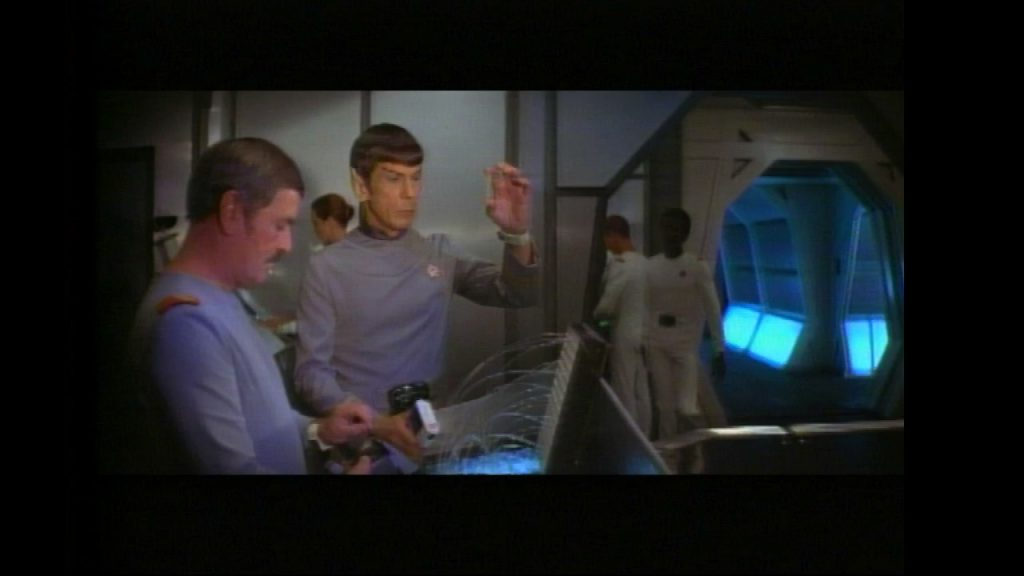 Spock holds up a vial while Scotty looks on